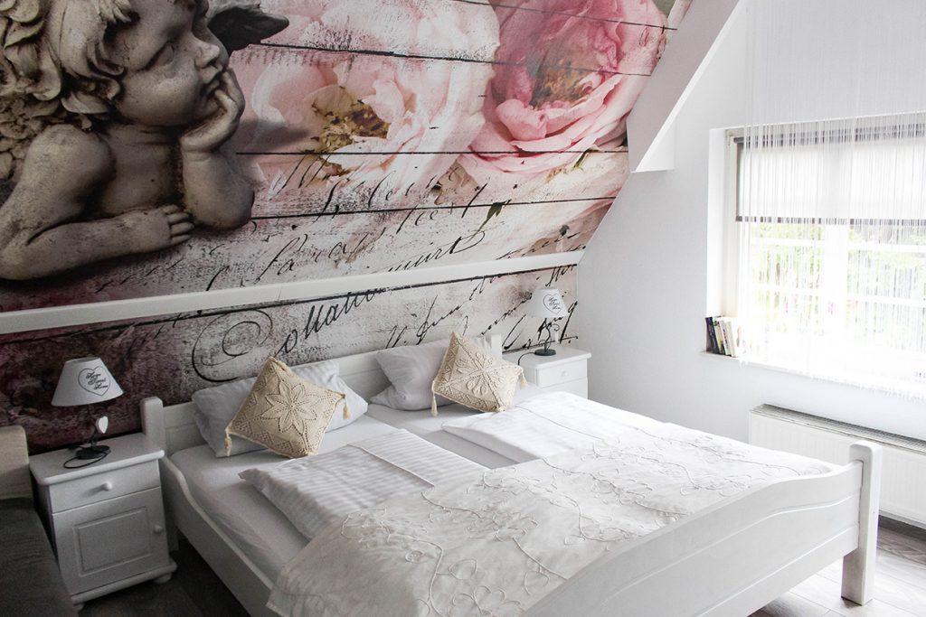 Doppelbett, Tapete mit Engel und Rose, Nachttisch, Nachttischlampe