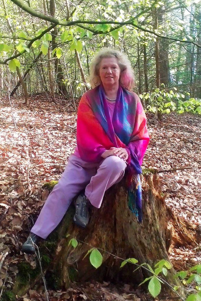 Wald, Frau sitzt auf Baumstumpf